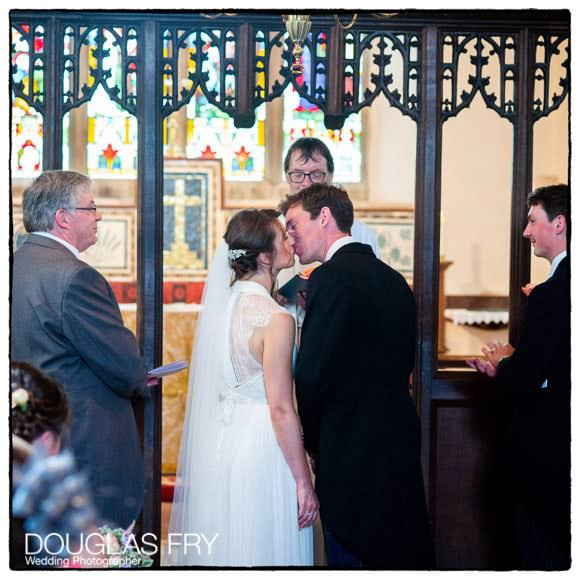 Bride and Groom kissing during wedding ceremony in Gloucestershire