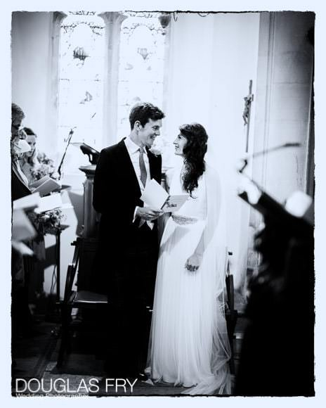 Black and white photograph of couple during wedding in Church