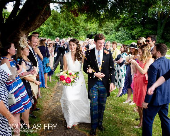 Couple leaving church with confetti - Gloucestershire