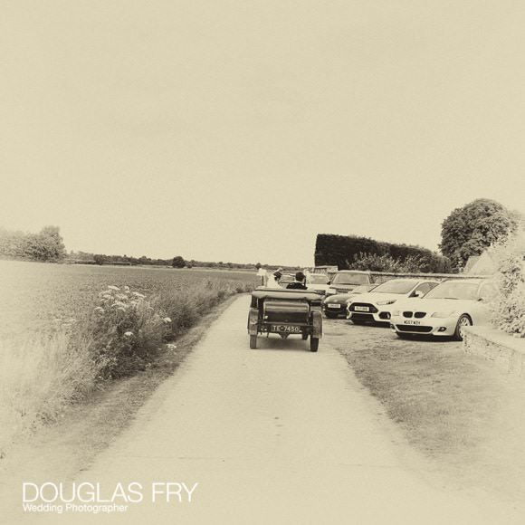 Couple driving to reception across field in vintage car