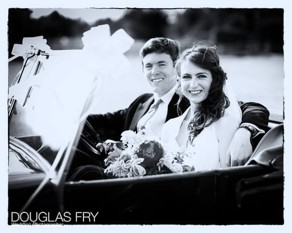 Black and white photograph of couple in wedding car