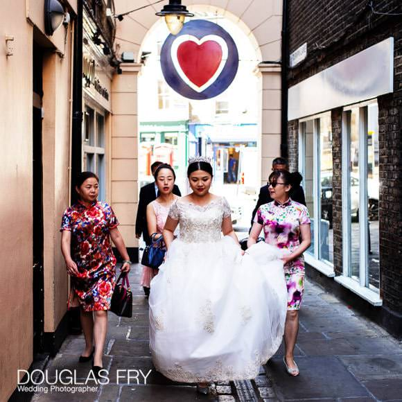 Bride walking through Greenwich Market beneath sign of heart