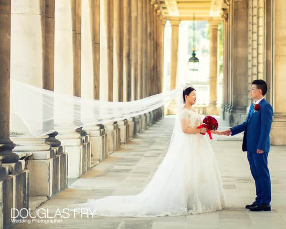 Bride with groom photographed amongst the colonades at Admirals House