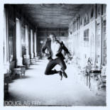 Groom pictured in black and white in Syon House after wedding ceremony - leaping in the air
