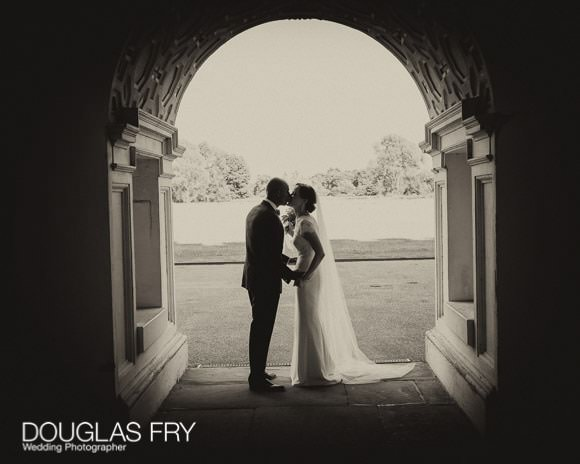 Couple pictured kissing under arch in black and white at Syon Park