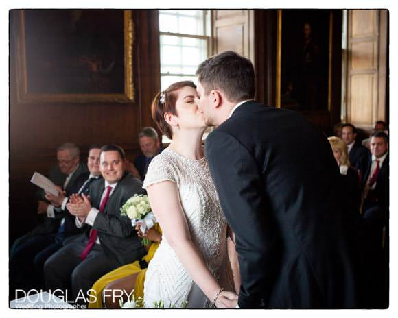 bride and groom kiss during wedding ceremony at the Admirals House
