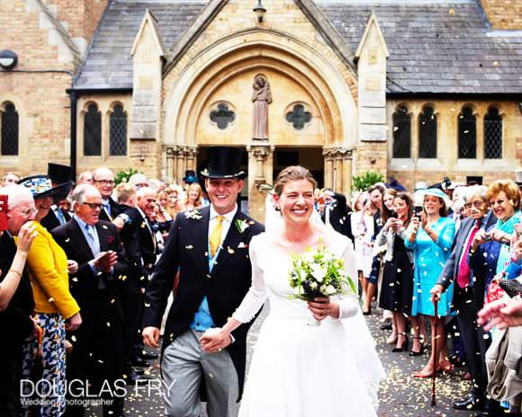 Bride and groom leaving church with confetti on wedding day