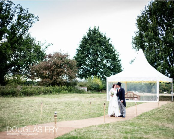 Bride and groom walking in gardens in front of marquee during wedding reception in Oxfordshire