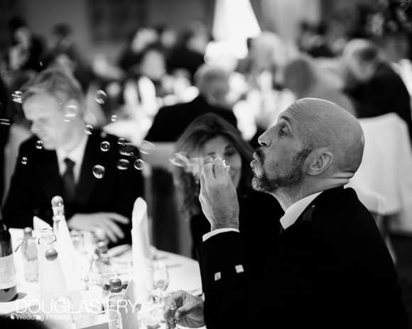 Guest blowing bubbles - photograph taken during wedding breakfast at Caledonian Club