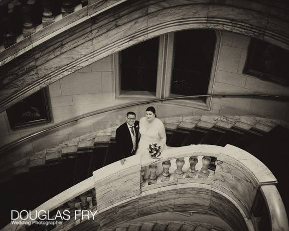 The couple photographed on the stairs at One Whitehall Place