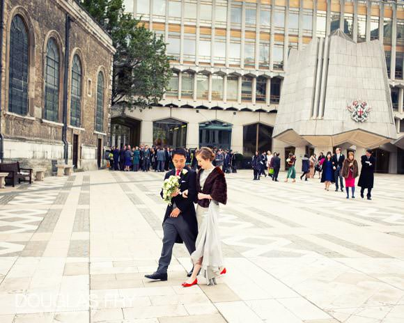 Bride and groom photogrpahed in front of St Lawrence Jewry walkibng through London
