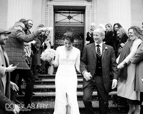 Black and white photograph of bride and groom on steps with register office with confetti