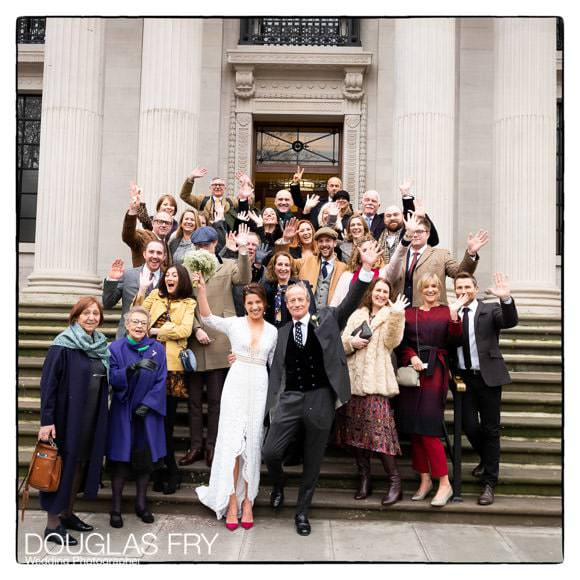 couple with wedding guests on Marylebone Town Hall steps - wedding photograph of group