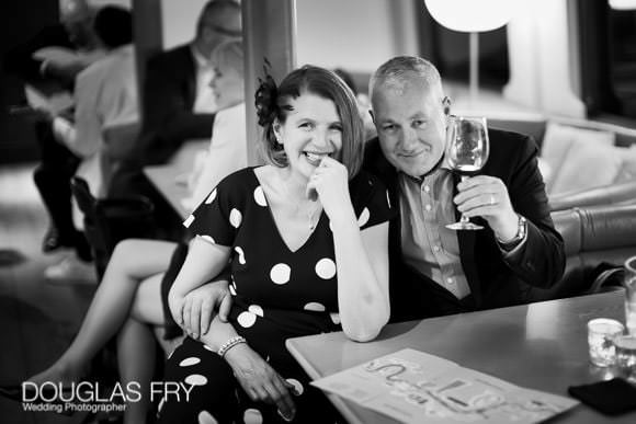 Friends on boat in London having a drink during wedding reception - black and white photograph