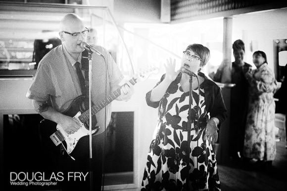 Guests enjoying the wedding and singing - black and white photograph