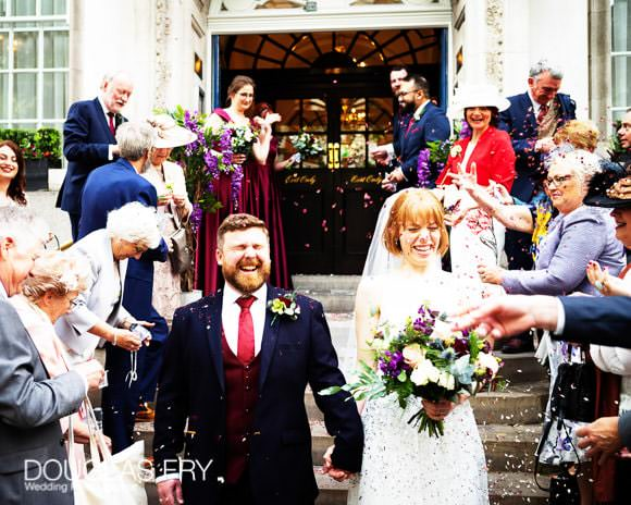 Bride and groom being showered with confetti on steps to Chelsea Register Office on the Kings Road in London