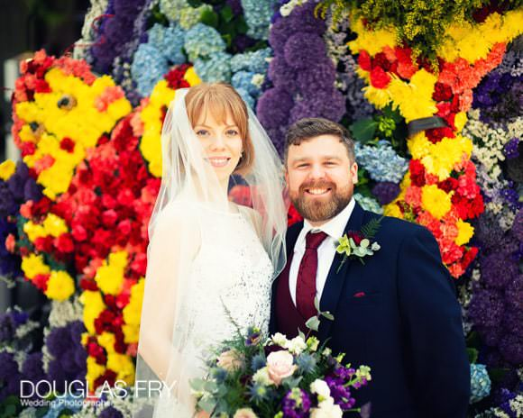 Bride and groom photographed in front of colourful floral display in Chelsea