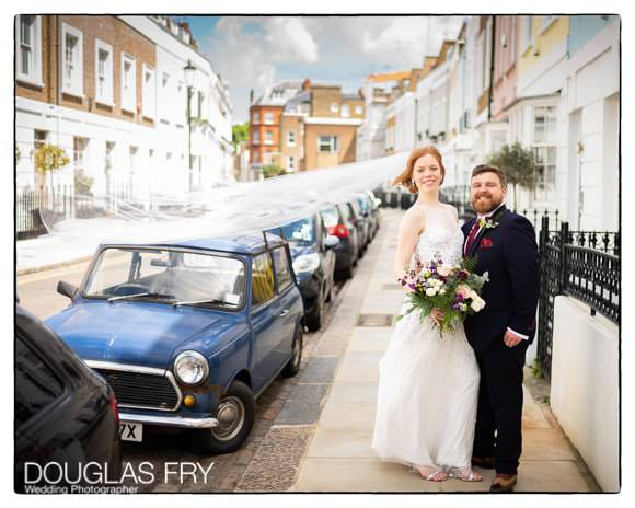 Bride and groom in Chelsea street with veil in the wind