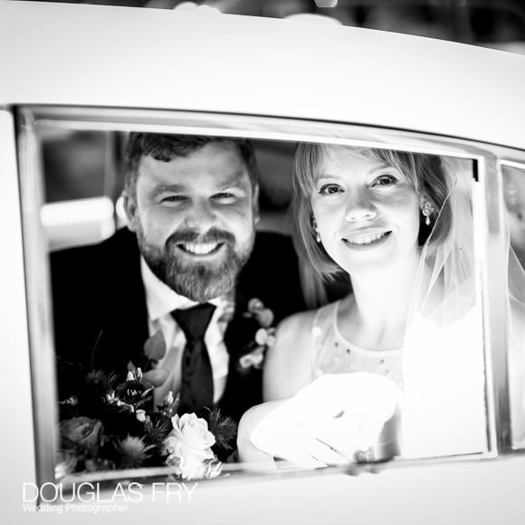 Couple in wedding car on way to reception in Barnes
