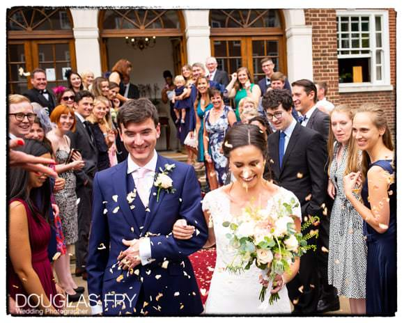 couple with confetti in front of london venue