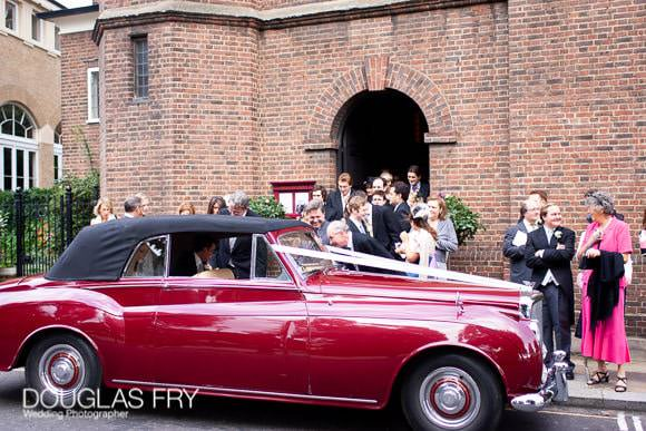 Wedding car leaving church after service in Chelsea