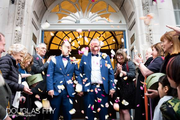 Wedding party photographed on the steps of Chelsesa Town Hall with confetti by Chelsea wedding photographer