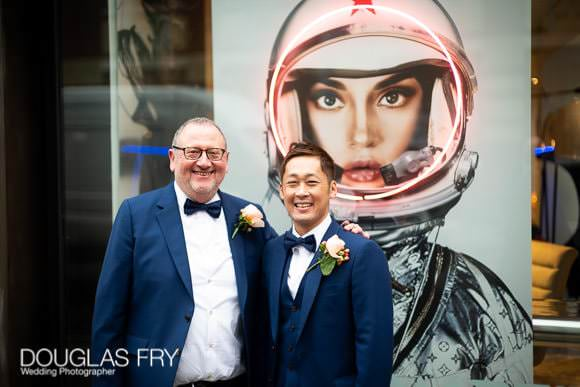 Couple photographed with fun murial behind