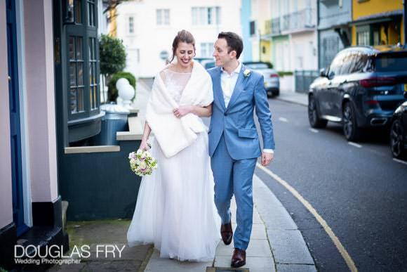 Couple phootgraphed on wedding day walking along Chelsea street