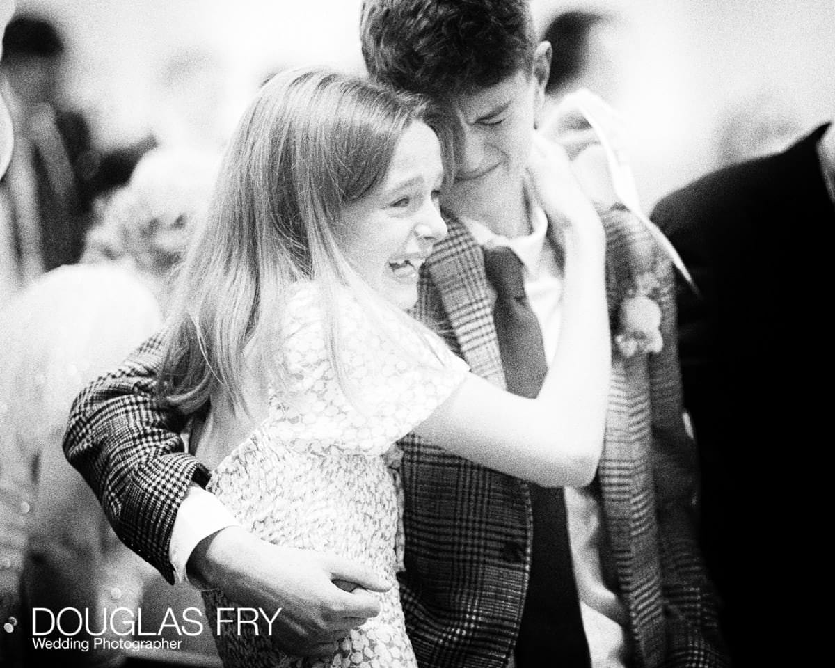 Emotional photograph of two children during wedding service at London Church