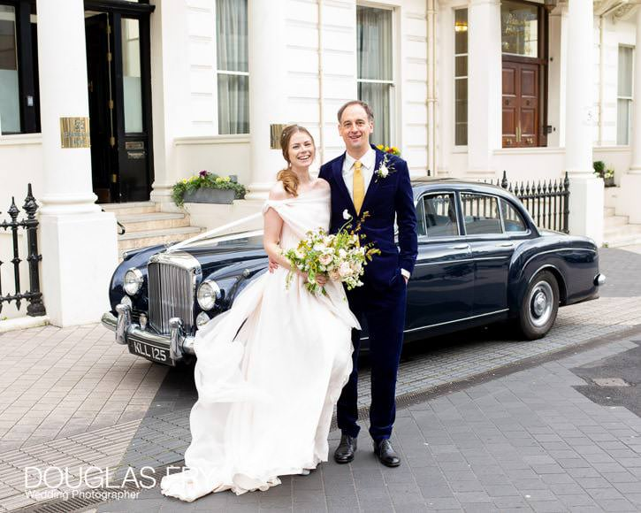 wedding couple pausing for photography outside Ognisko in London with the fabulous Bentley car