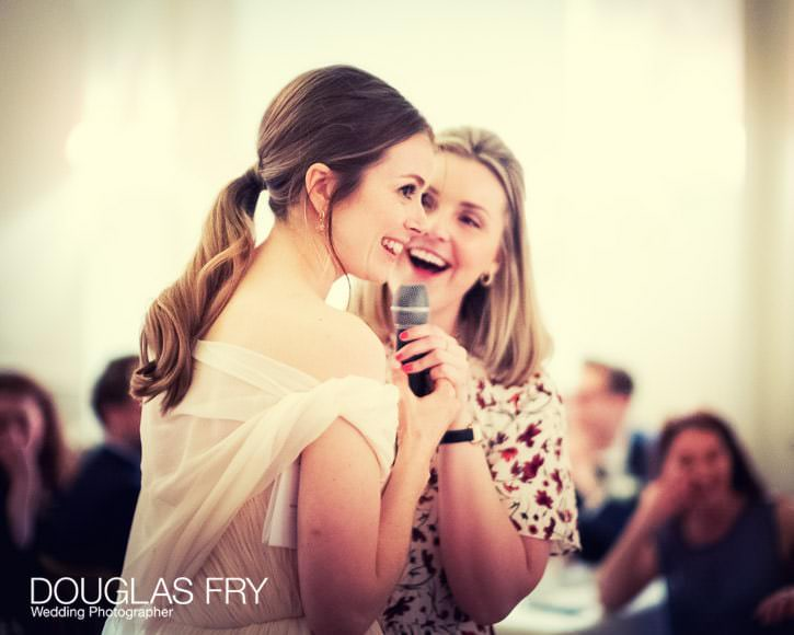 The bride and a friend from school share a fun memory with the guests