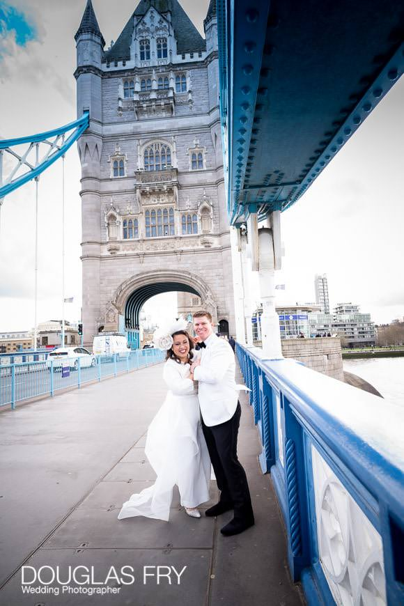 wedding couple pause for portraits on Tower Bridge, London before going in for service