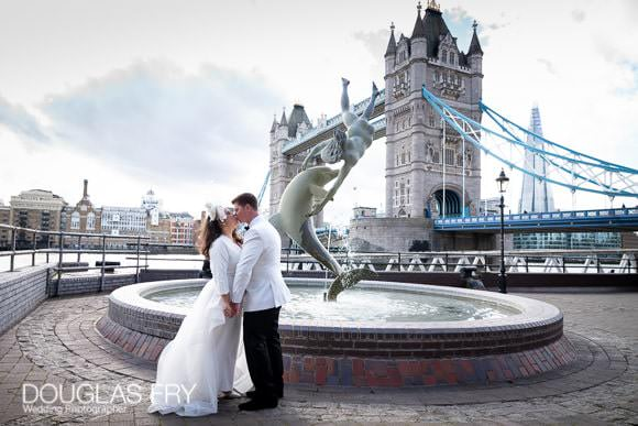 Wedding couple pose next to the boy with dolphin statue next to Tower Bridge