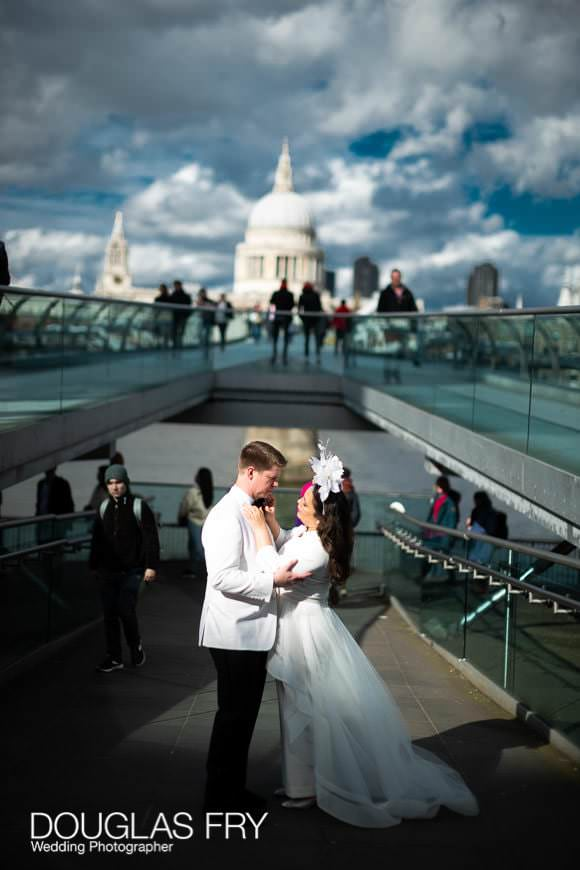 Wedding couple caught in sunshine on the Millenium Bridge on London's South Bank