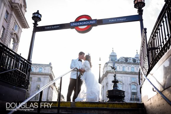 Couple pose for a wedding photograph at Piccadilly Station to include the statue of Eros