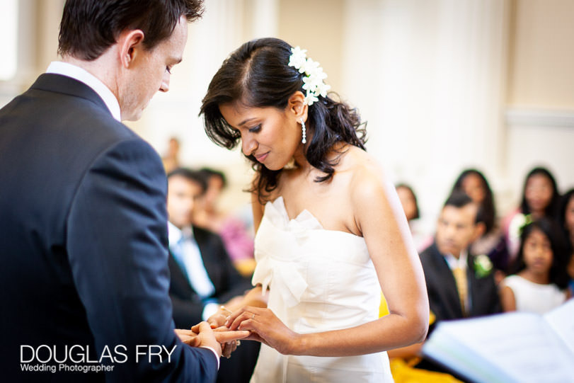 syon park wedding ceremony - bride putting ring onto groom's finger
