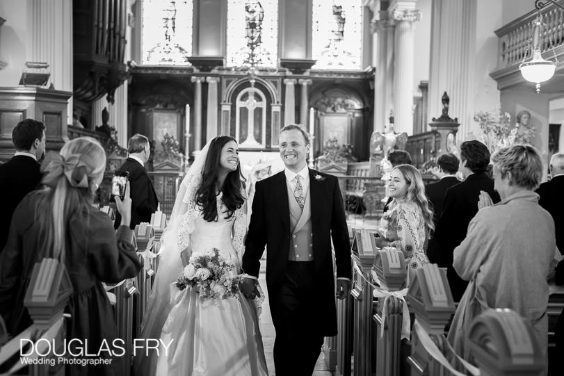 Black and white wedding photograph of couple walking down aisle i hampstead parish church