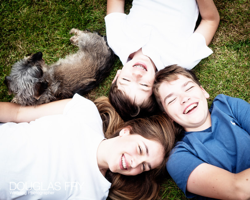 Teenage children and dog photographed at home in Wiltshire on the lawn