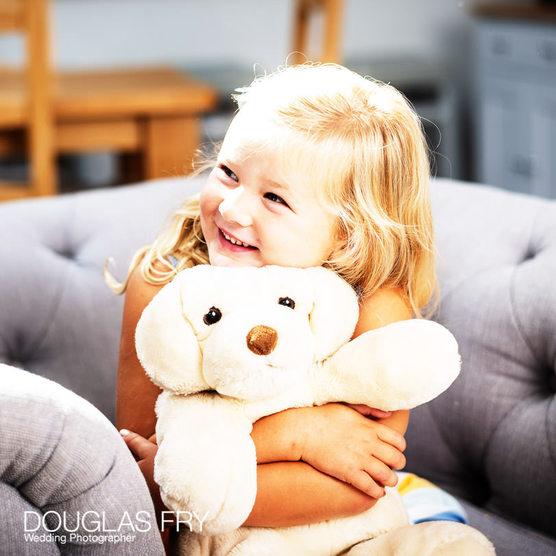 Girl with teddy on sofa at home during family photo shoot