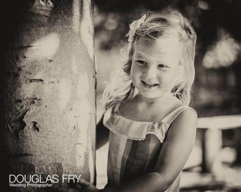 Daughter looking around tree in the garden