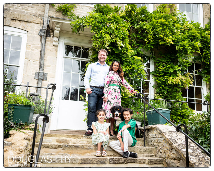 Family photographed in front of family home with dog