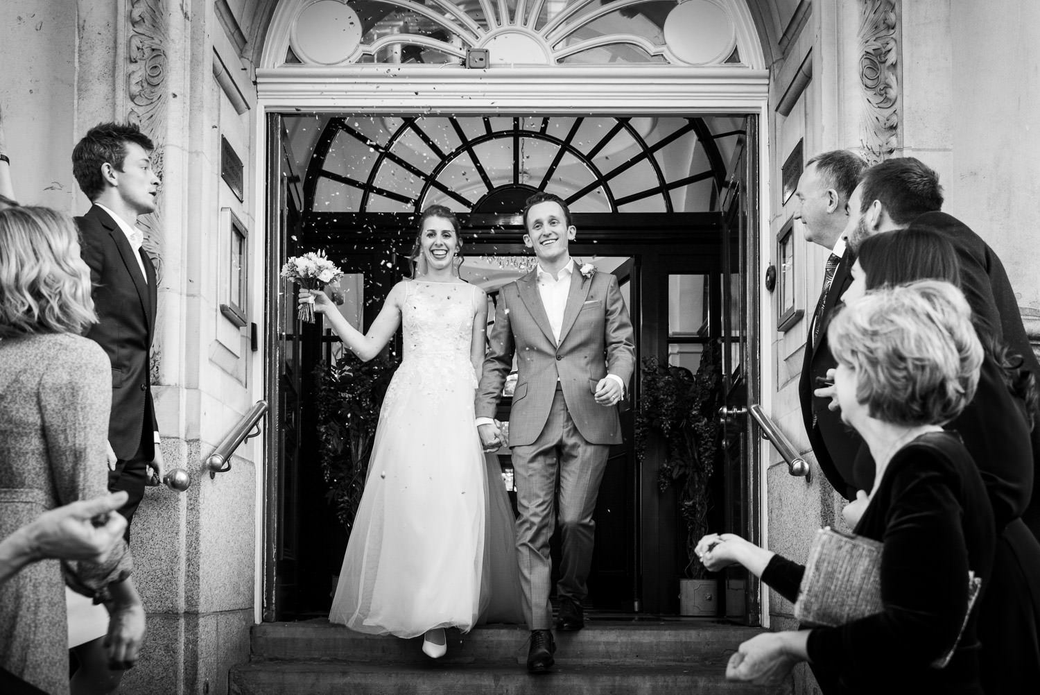 Couple during wedding at Chelsea Register Office photographed on the steps with confetti