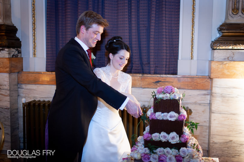 Wedding Photographer One Great George Street London - cutting the wedding cake