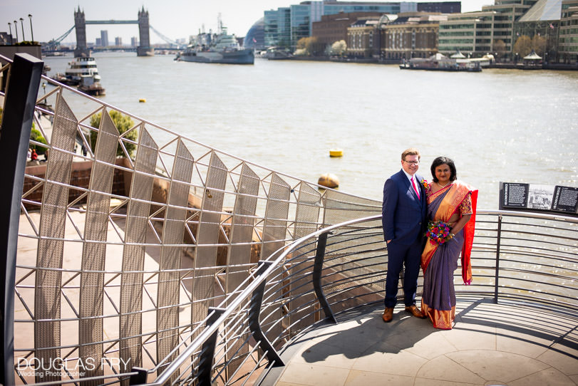 Bride and groom photographed together with Tower Bridge behind