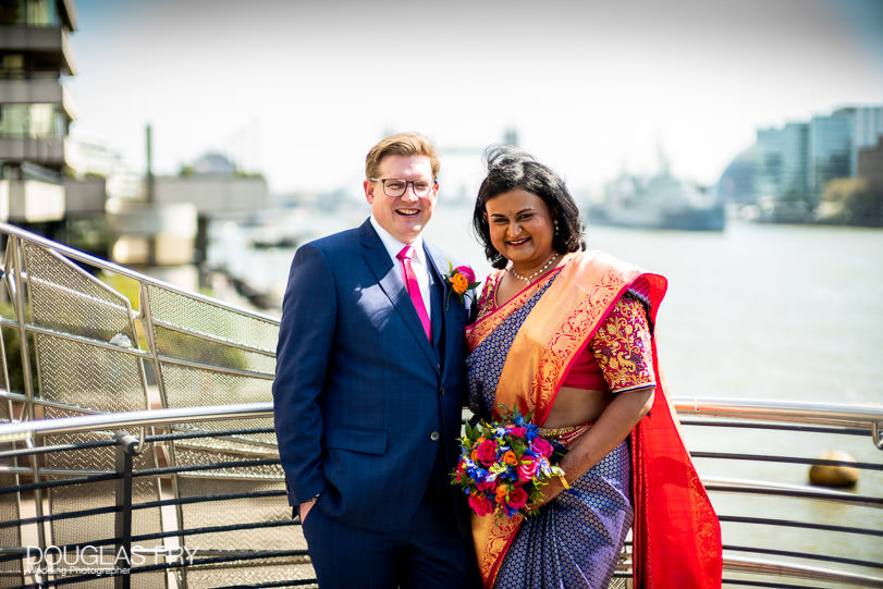 Bride and groom photographed together by the Thames in London