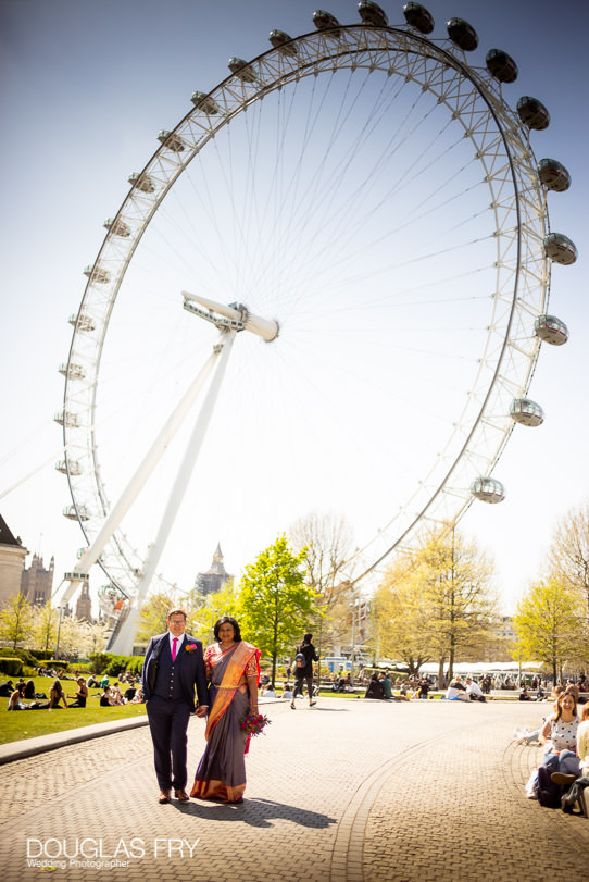 Bride and groom photographed together in front of the London Eye