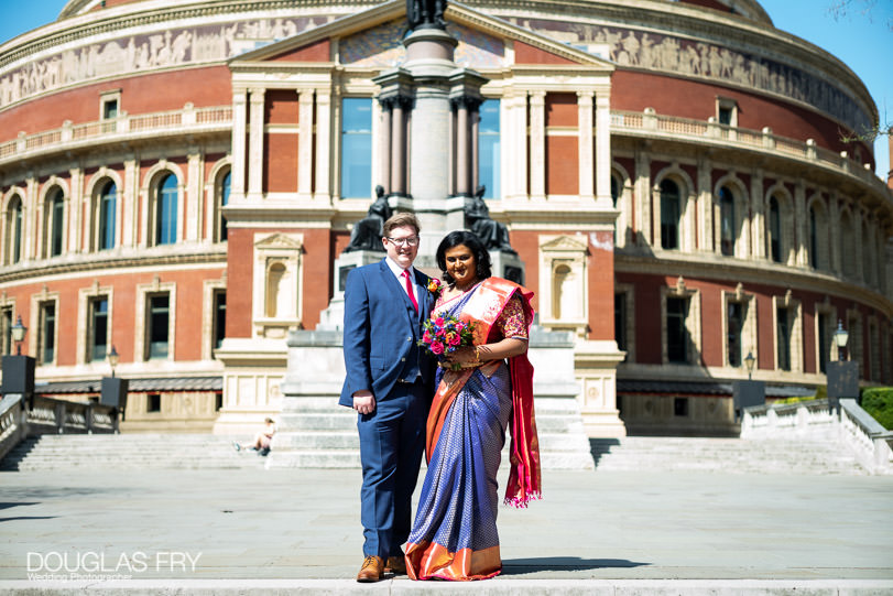 Bride and groom photographed together on the steps of the Albert Hall in London
