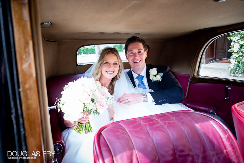 Wedding photograph of couple in wedding car going to reception in Chelsea Physic Garden