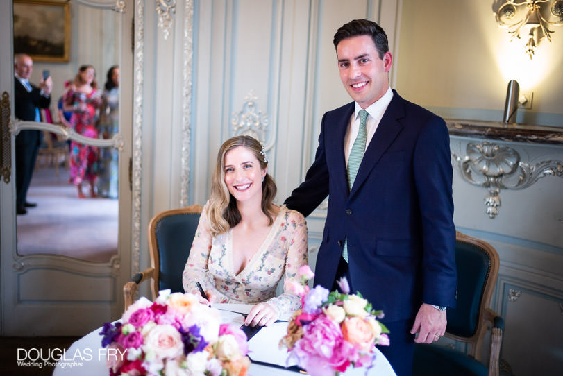 wedding couple signing regiser at Savile Club in London